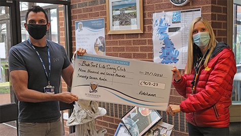 Headteacher Mr Wilkes passing the cheque over to Mrs Bardsley